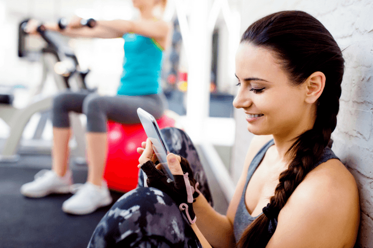female personal trainer checking her phone in the gym