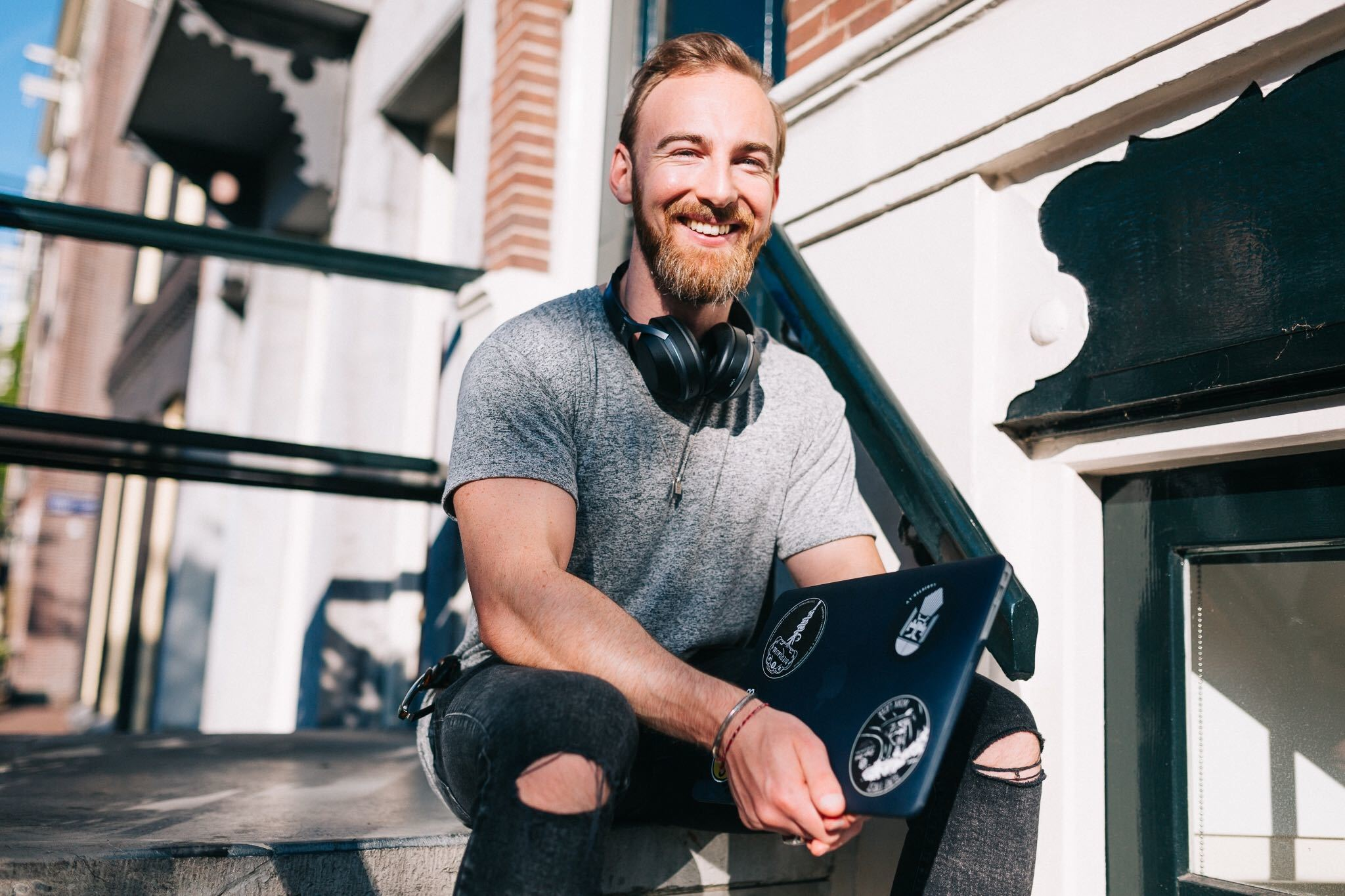 Ru Anderson holding his laptop with a smile to start his high ticket online personal training